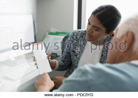 Female doctor showing brochure to senior male patient in clinic office - Stock Photo