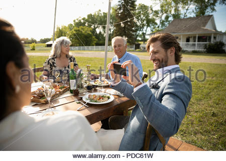 Man with camera phone photographing friends at sunny, rural garden party lunch - Stock Photo
