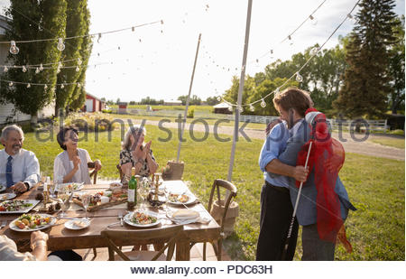 Friends clapping for son giving golf club to father at retirement party in sunny rural garden - Stock Photo