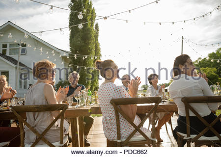 Friends clapping, celebrating at garden party table - Stock Photo