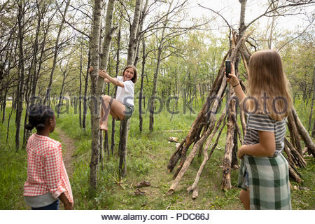Tween girl friends with camera phone climbing tree, playing in woods - Stock Photo
