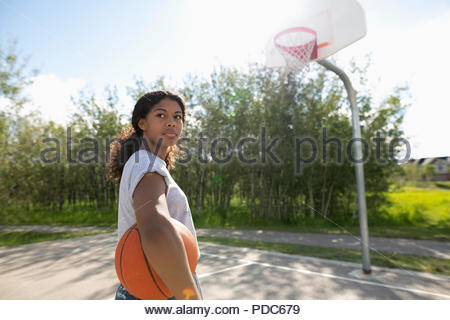 Confident, tough young woman with basketball at park basketball court - Stock Photo