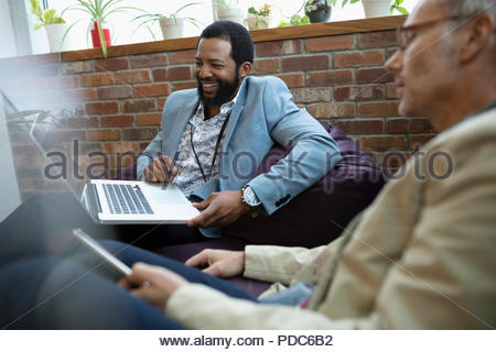 Smiling creative businessmen using digital tablet and laptop on beanbags in office - Stock Photo