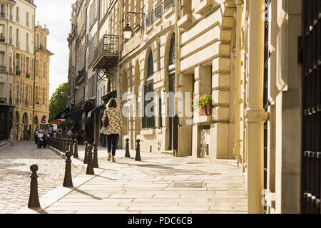 Paris street scene - a woman walking along the Place Dauphine on the Ile de la Cite in Paris in late afternoon, France, Europe. - Stock Photo