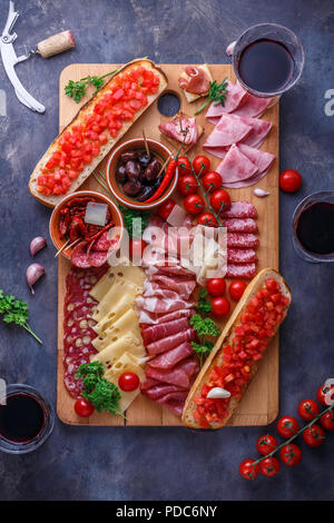Board of cured meat, cheese and bread with wine - Stock Photo