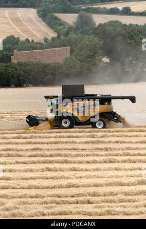 Whitchurch, Hampshire, England, UK. Modern combine harvester working in a field of wheat - Stock Photo