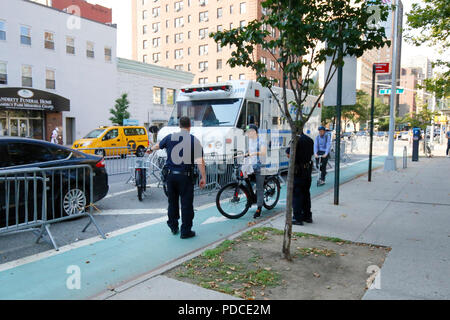New York, NY, USA. 8th August, 2018.  Police direct a cyclist with a Class 2 electric bicycle--throttle assist--to a holding cage next to the Second Avenue bike lane in Manhattan. Electric bikes are currently illegal in New York State. NYC Mayor DeBlasio has directed the Department of Transportation to begin allowing Class 1 pedal assisted electric bikes, while continuing the crackdown on all e bikes.  Most electric bike users are food delivery personnel. - Stock Photo