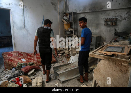 Gaza. 9th Aug, 2018. Palestinians inspect a damaged house where a pregnant mother and her baby girl were killed while the father wounded after Israeli airstrikes, in central Gaza Strip town of Deir el-Ballah, on Aug. 9, 2018. Israel on Wednesday carried out large-scale airstrikes in the Gaza Strip, targeting '12 terror sites,' a military spokesperson said in a statement. Credit: Stringer/Xinhua/Alamy Live News - Stock Photo
