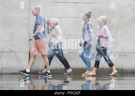 London UK. 9th August 2018. Pedestrians wearing ponchos  shelter from the rain in Trafalgar Square  on a wet day as the rains arrive to break the hot spell and summer heatwave Credit: amer ghazzal/Alamy Live News - Stock Photo