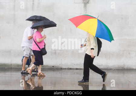 London UK. 9th August 2018. Pedestrians and tourists brave the rain in Trafalgar  Square with ponchos and umbrellas on a wet day as the rains arrive to break the hot spell and summer heatwave Credit: amer ghazzal/Alamy Live News - Stock Photo