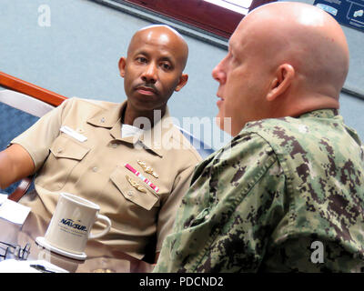 """180803-N-PX557-018  MECHANICSBURG, Pa.  (Aug. 3, 2018)  Capt. Douglas M. Bridges Jr., commanding officer, Naval Supply Systems Command (NAVSUP) Business Systems Center (BSC), listens to Rear Adm. Kevin M. Jones, commander, Defense Logistics Agency Distribution, during a mentoring session at NAVSUP BSC in Mechanicsburg, Pa., Aug. 3. The session was part of a series, """"Mentoring without End,"""" which brings together senior and junior Supply Corps officers in the Mechanicsburg area to share experiences, network, and collaborate.   (U.S. Navy photo by James E. Foehl/Released) - Stock Photo"""