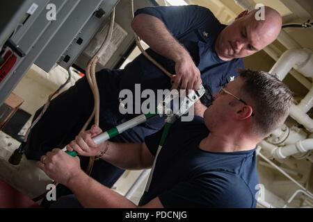 180804-N-AV754-0058 TALLINN, Estonia (Aug. 4, 2018) Electrician's Mate 2nd Class Matthew Holland, left, and Chief Electrician's Mate Chadwick Bradley repair electrical equipment aboard the Arleigh Burke-class guided-missile destroyer USS Winston S. Churchill (DDG 81), Aug. 4, 2018. Winston S. Churchill, homeported at Naval Station Norfolk, is conducting naval operations in the U.S. 6th Fleet area of operations in support of U.S. national security interests in Europe and Africa. (U.S. Navy photo by Mass Communication Specialist 2nd Class Evan Thompson/Released) - Stock Photo