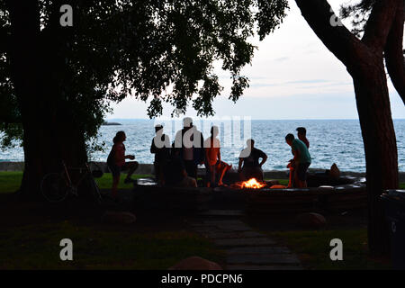 Students from the University of Chicago are silhouetted against Lake Michigan in the evening as they gather around a fire pit on Promontory Point. - Stock Photo