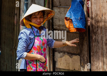 Ho Chi Minh City, Asia - May 12, 2018: Portrait of a woman wearing a vietnamese hat in Saigon - Stock Photo