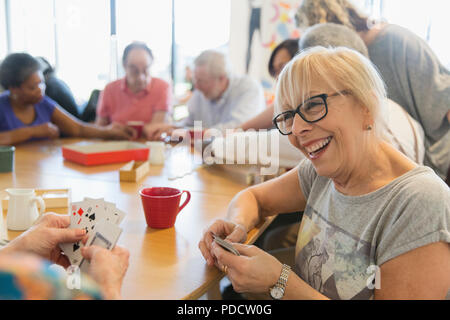 Happy senior woman playing cards with friend at table in community center - Stock Photo