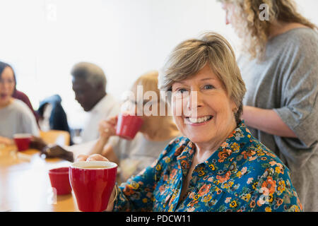 Portrait smiling, confident senior woman drinking tea with friends in community center - Stock Photo