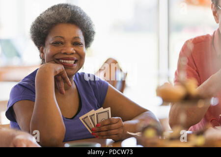 Portrait smiling, confident senior woman playing cards in community center - Stock Photo