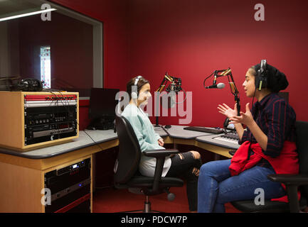 Teenage musicians recording music in sound booth - Stock Photo