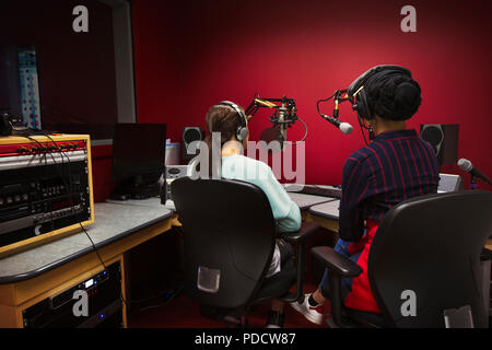 Teenage girl musicians recording music, singing in sound booth - Stock Photo
