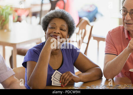 Confident, happy senior woman playing cards with friends in community center - Stock Photo