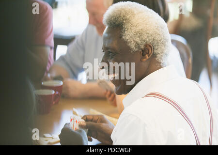 Happy senior man playing cards in community center - Stock Photo