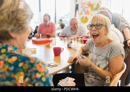 Happy senior woman playing cards with friend in community center - Stock Photo