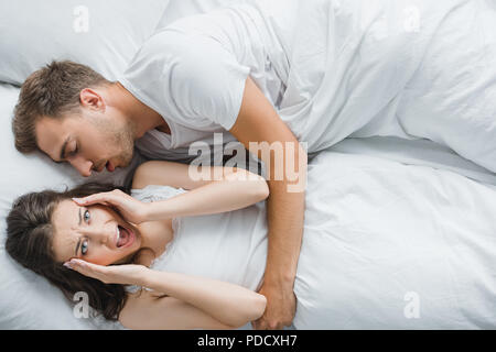 top view of young angry woman having headache and screaming while lying with snoring husband in bed - Stock Photo