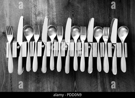 lots of knives forks and spoons staked in a line in five wooden cutlery holders on a wooden table top, black and white photograph - Stock Photo