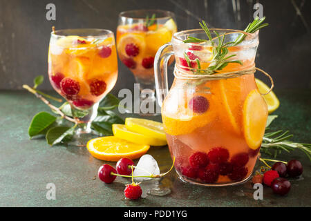 Homemade refreshing wine sangria or punch with fruits in glasses. Sangria cocktails with fresh fruits, berries and rosemary. On a stone or slate backg - Stock Photo