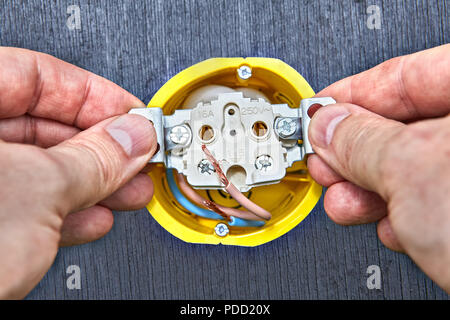 Installation of wall electric socket in yellow outlet box of domestic electrical wiring. - Stock Photo
