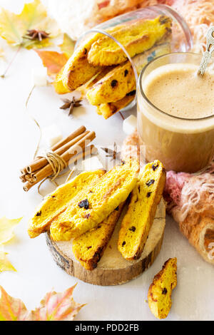 Autumn background baking. Freshly baked raisins and cinnamon biscotti and a cup of cappuccino coffee on light slate or slate background. - Stock Photo