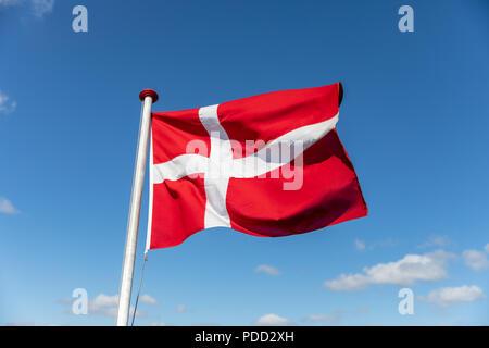 Danish flag against blue sky - Stock Photo