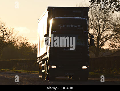Scania HGV on A-road silhouetted by sun