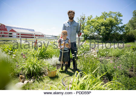 Portrait smiling father and son gardening on sunny rural farm - Stock Photo