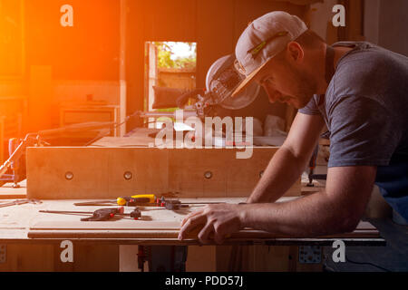 Experienced carpenter in work clothes and small buiness owner working with wood in workshop - Stock Photo