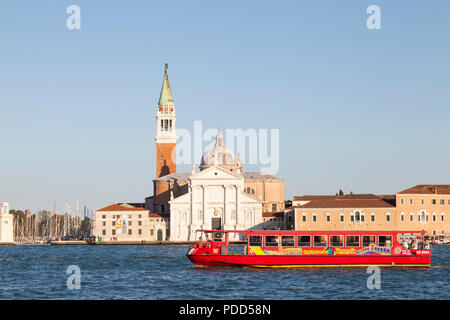 Colourful red Venezia City Sightseeing Tour Boat passing San Giorgio Maggiore, Venice, veneto,  Italy at sunset in the Giudecca Canal - Stock Photo