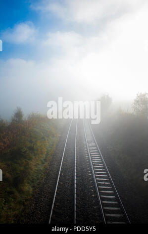 Railway track disappearing into the horizon on a sunny day in Cumbria, England. - Stock Photo