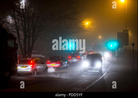 Traffic driving on a Winter's night on a street in England. - Stock Photo