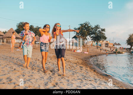 Portrait of happy children having fun while walking on the shore - Stock Photo