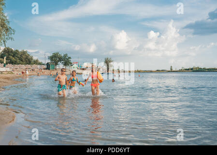 Happy joyful little children playing in the sea, with pleasure splashing the water, enjoying summer holidays on the beach resort, travel and tourism c - Stock Photo