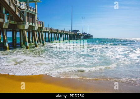 A view of blue ocean waves on the shore of the beach at Jeanette's Pier on the Outer Banks in North Carolina. - Stock Photo