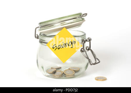 Slush fund: glass clip top Kilner storage jar with British one pound coins and stickie post-it note with word Savings - Stock Photo