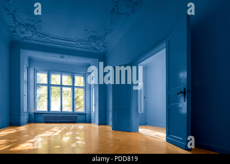 empty room in old apartment building with  parquet floor  and blue painted walls   - - Stock Photo