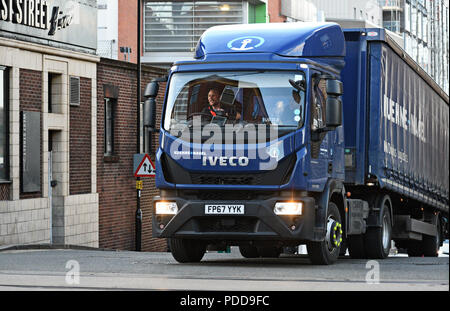 Kuehne and Nagel Iveco curtainsider truck crosses West Street in Sheffield, UK - Stock Photo