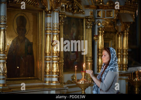 Russian beautiful Caucasian woman with red hair and a scarf on her head is in the Orthodox Church, lights a candle and prays in front of the icon - Stock Photo