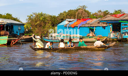 A Cambodian woman is transporting children from one house to another in floating village near Siem Reap, Cambodia - Stock Photo