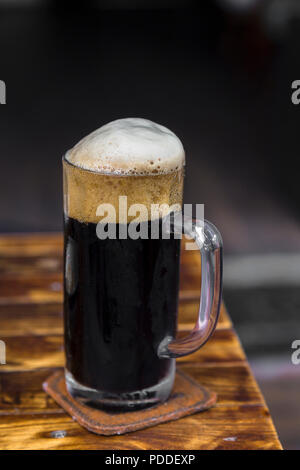 Dark German draft beer served in a mug with a head and a dark backgound in a DaLat Vietnames Pub. - Stock Photo