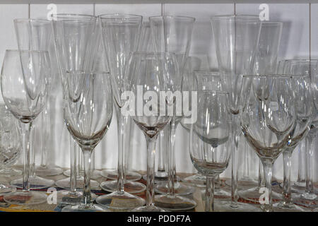 Wine glasses of various shapes and sizes standing on a sheet of newspaper on a cupboard shelf - Stock Photo