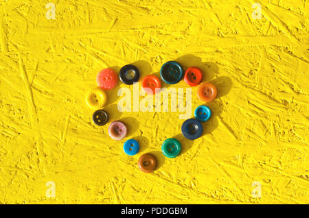 heart made of buttons. the concept of love. yellow background.needlework, hobby, creative, antiques - Stock Photo