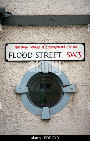 street name sign for flood street, chelsea, london, england, above a porthole window - Stock Photo